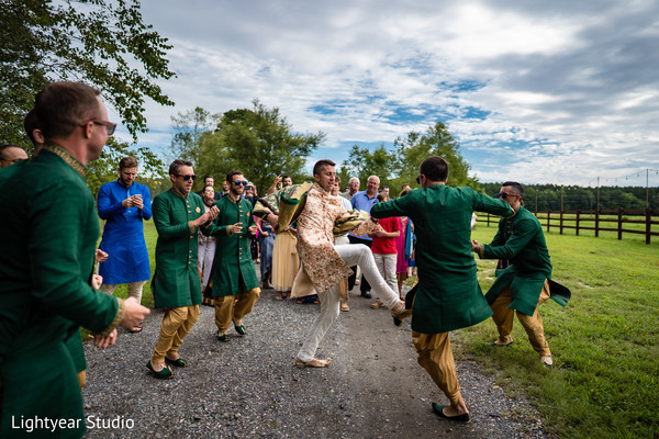 Groom dancing along with groomsmen during baraat