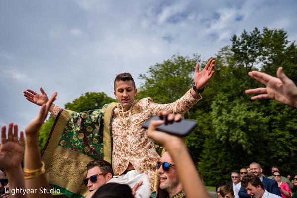 Groom carried in groomsmen arms during baraat