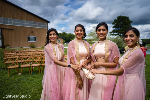 Indian bridesmaids holding shoe
