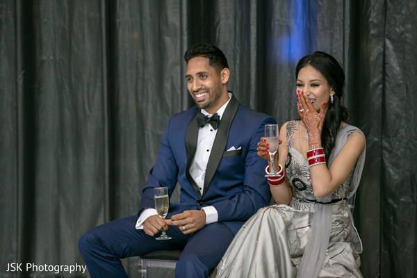 Indian couple at wedding reception cheers.