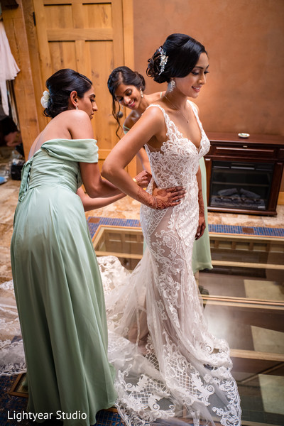 Bride getting dressed in her gorgeous white gown.