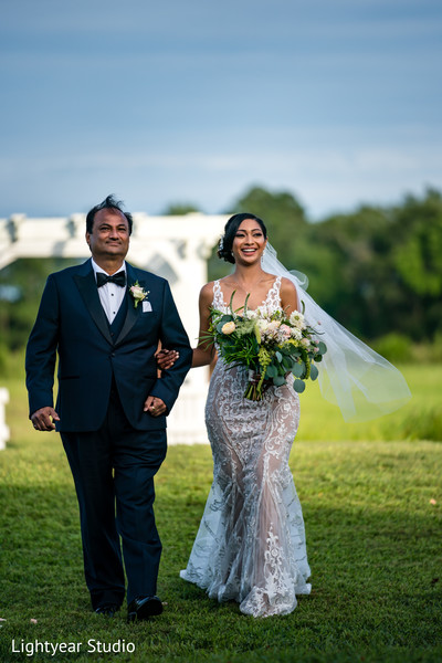Bride walking down the aisle in the company of her father