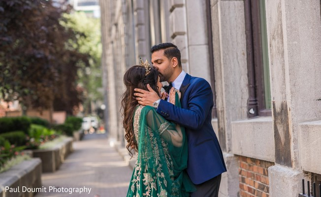 Sweet capture of Indian groom kissing his bride on the forehead