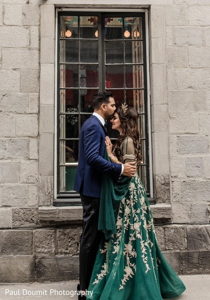 Handsome Indian groom kissing bride in the forehead