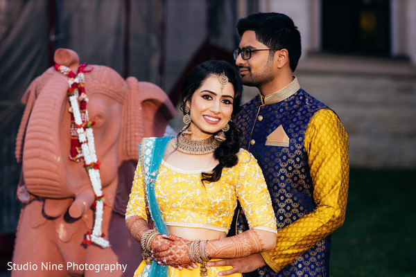 indian bride and groom wearing yellow sangeet outfits.