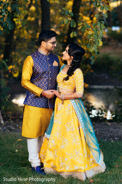 indian couple posing out doors for sangeet photo session.