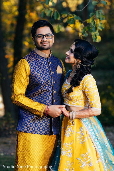 Indian groom and bride in their yellow  sangeet outfits.