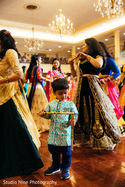 Indian sangeet guests dance with dandiya sticks.