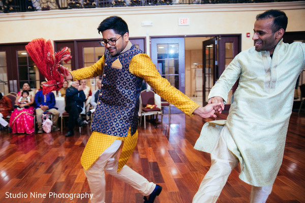 Indian groom dancing at sangeet party.