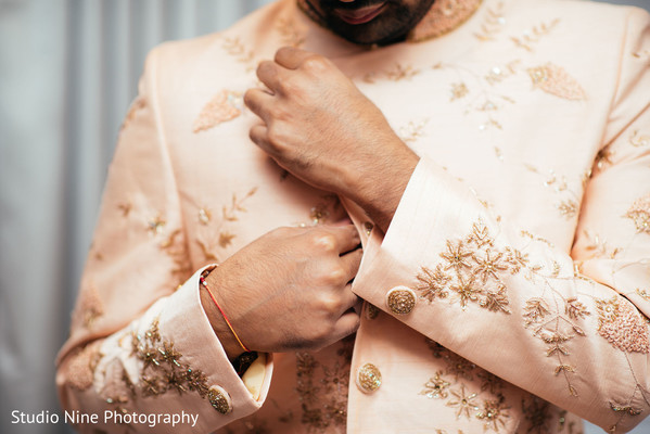 Indian groom's pale peach sherwani with golden embroidery.
