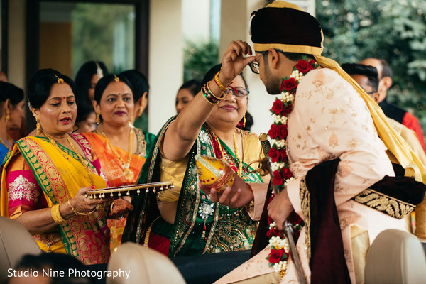 Indian groom getting the red dot on forehead.