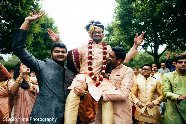 Indian groom lifted by groomsmen.
