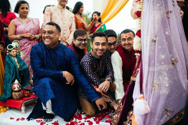 Indian groomsmen at wedding ceremony ritual.