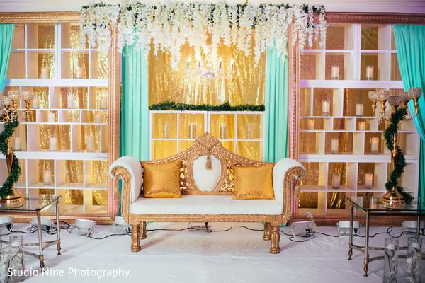 Indian wedding reception stage golden decoration.
