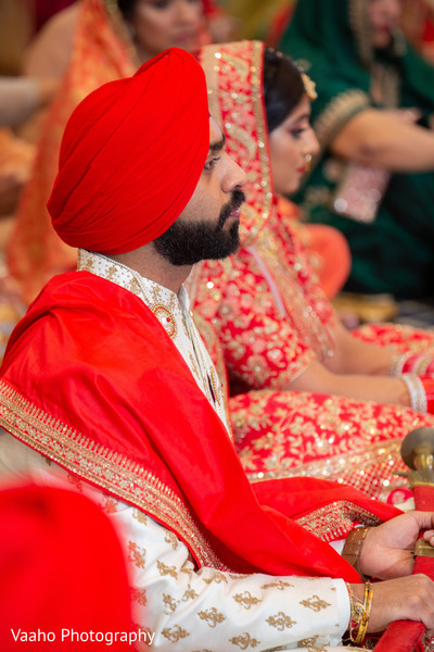 Indian groom in his red, golden and white ceremony outfit.