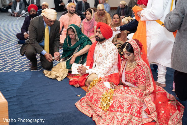 Indian couple siting infront of Sikh wedding altar.