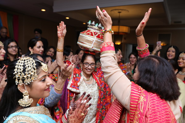 Indian bridal's mother iwth decorated jar on her head.