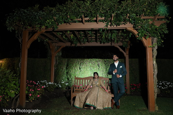Indian couple posing outdoors in a pergola.