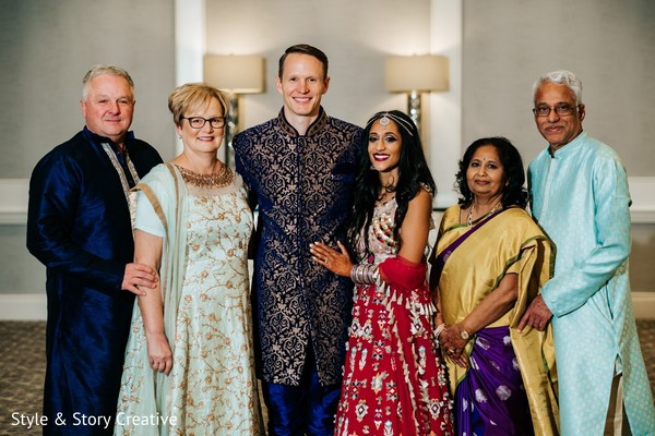 Indian couple posing with relatives at sangeet.