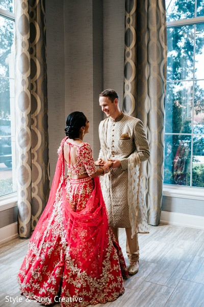 Indian bride and groom holding hands indoors.