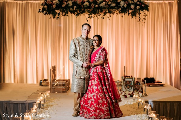 Indian couple posing under the mandap flowers.