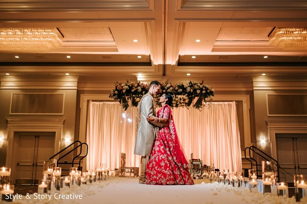 Indian couple posing at indian wedding aisle.