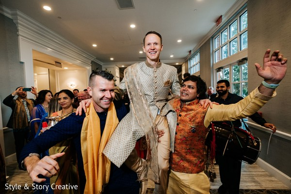Indian groom lifted by groomsmen at baraat party.