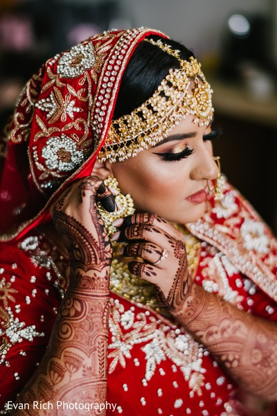 Indian bride putting on her golden Kundan earrings.