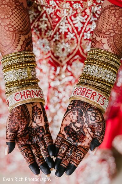 Indian bridal henna art and golden bangles.