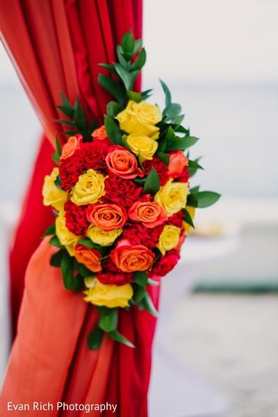 Red, yellow, and orange Indian wedding mandap flowers.