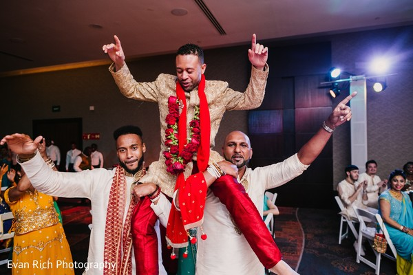 Indian groom lifted by groomsmen.