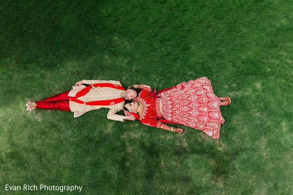 Indian bride and groom laying on the grass capture.