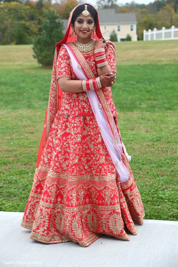Indian bride possing in her red and golden lehenga.