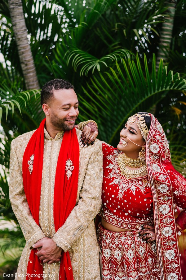 Indian couple posing in their red, and ivory ceremony outfits.