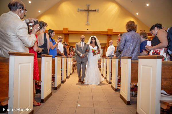 Bride walking down the aisle on her white wedding dress