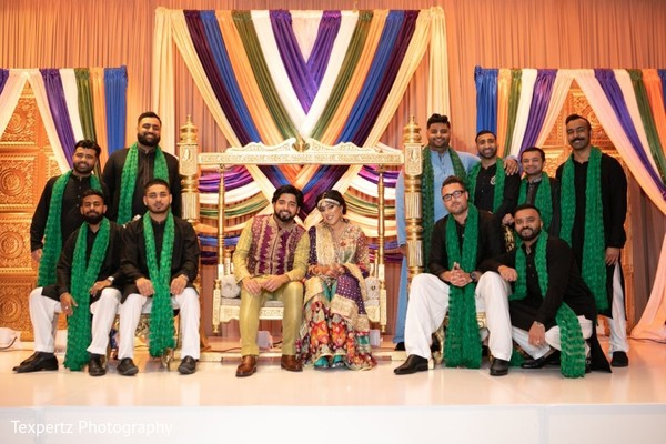 Sweet Indian couple posing with groomsmen during at the Mehndi