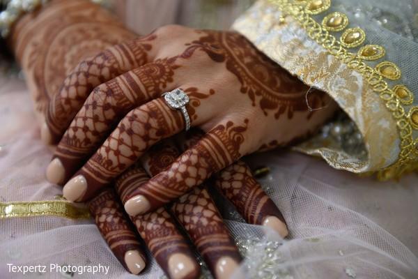 Close captured of bridal Mehndi and wedding ring.