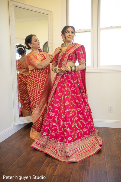 Sweet Indian bride's mother helping her to get ready