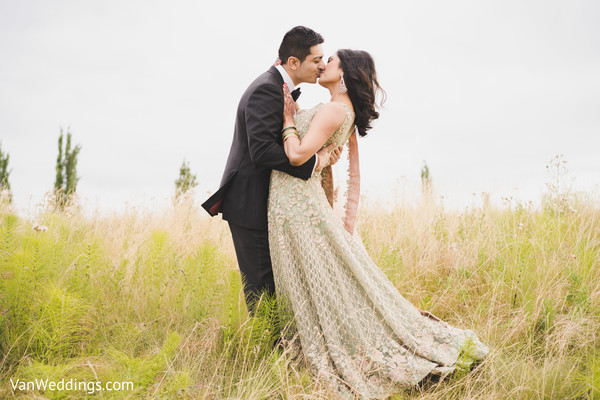 Lovely Indian groom kissing bride during the outdoor photo session.
