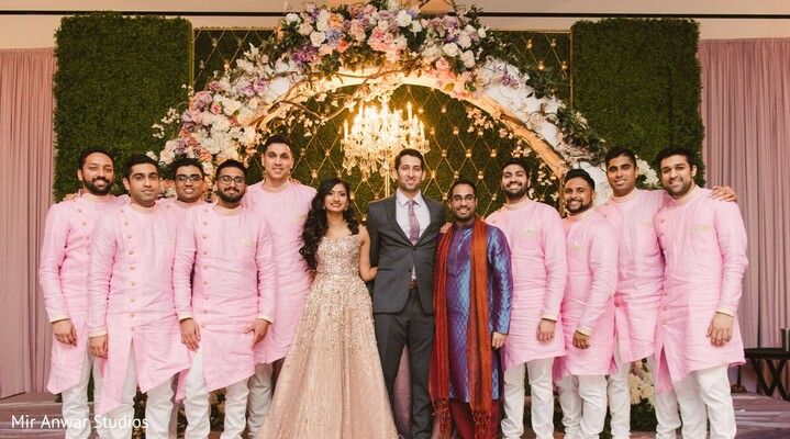 Indian couple possing for a reception photo with groomsmen.