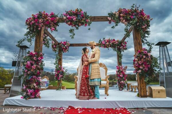 Indian bride and groom posing inside mandap.