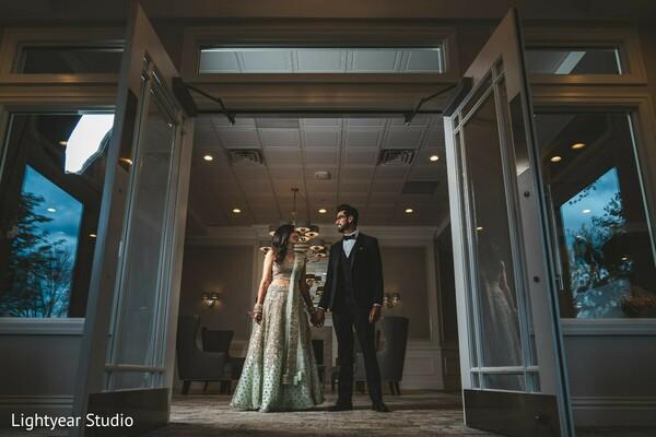 Indian couple posing between reception doors.