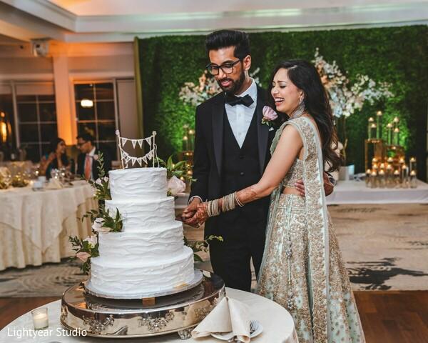 Maharani and raja cutting out Indian wedding reception cake.