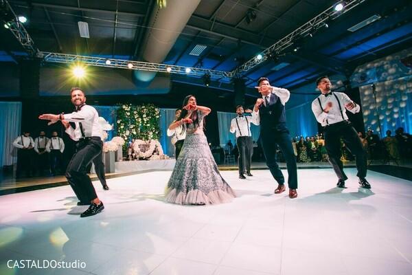 Indian bride with groomsmen dancing.