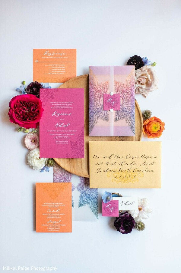 Indian wedding invitation in peach, pink and yellow color.