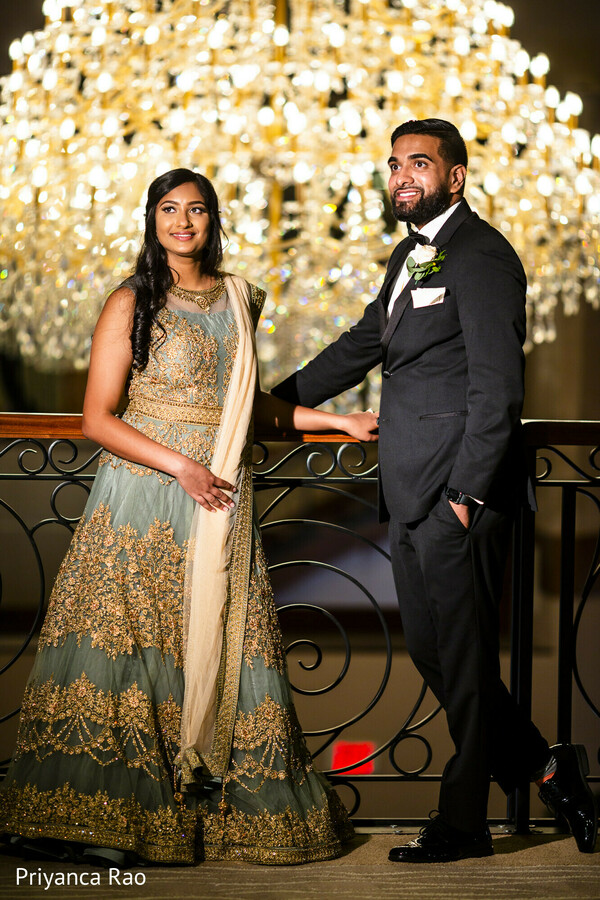 Indian bride next to groom on their wedding reception outfits.