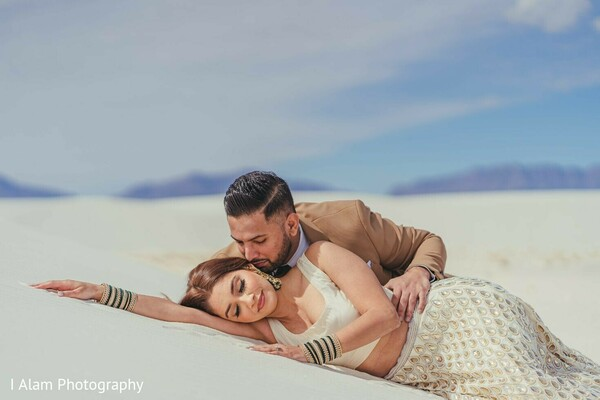 Indian bride and groom laying on white sand.