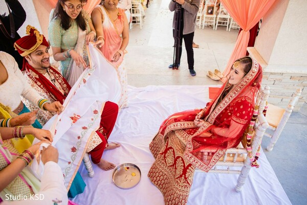 Indian bride and groom separated by an antarpat.