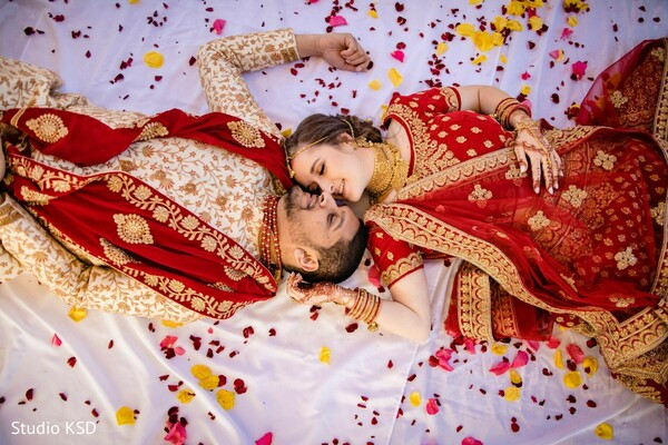 Indian couple on their red and golden wedding outfits.