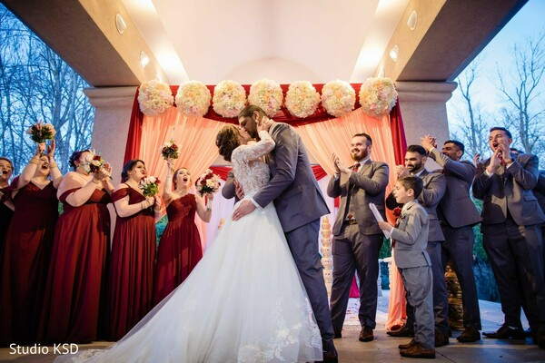 Indian groom kissing Indian bride photo.
